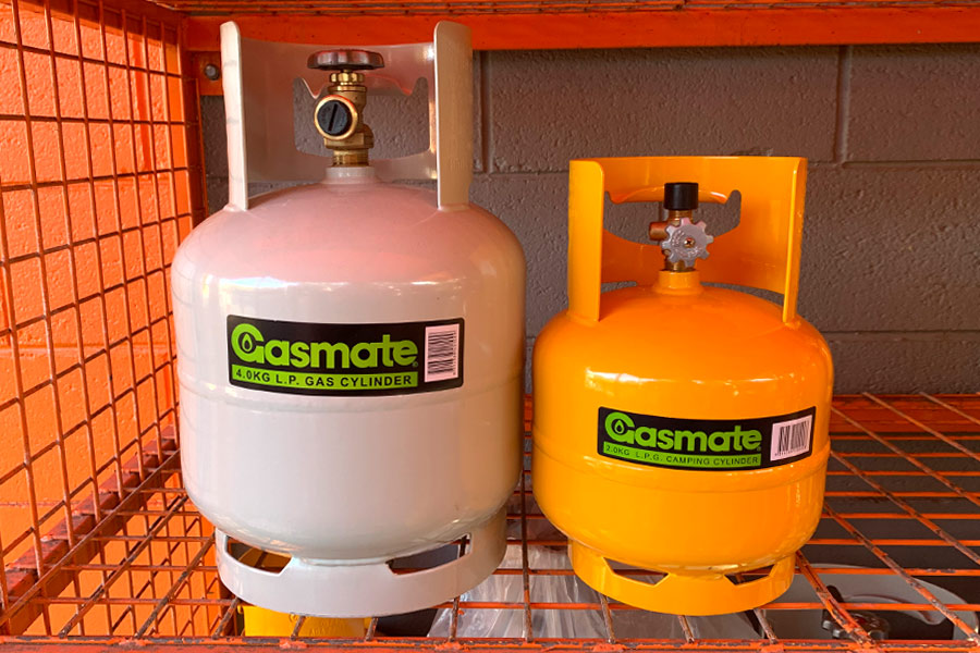 "POL 4kg gas cylinder next to a 3/8 "" BSP 2kg gas cylinder in a cage"