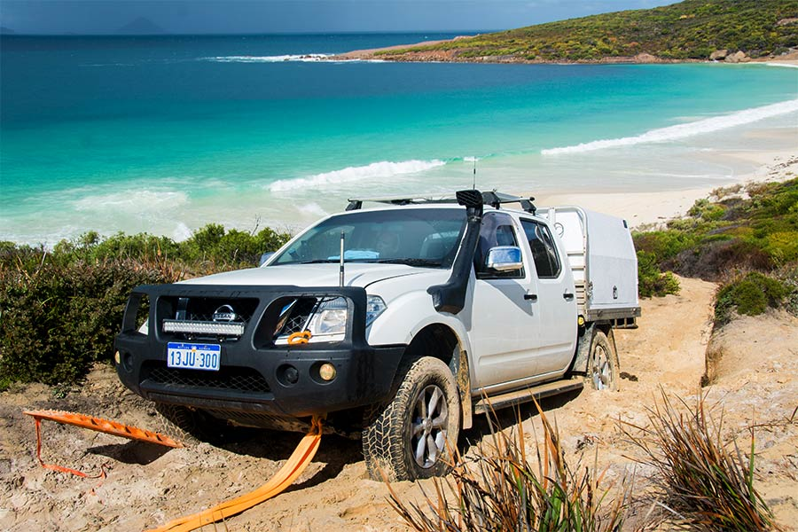 4wd towing a trailer on sand near the ocean