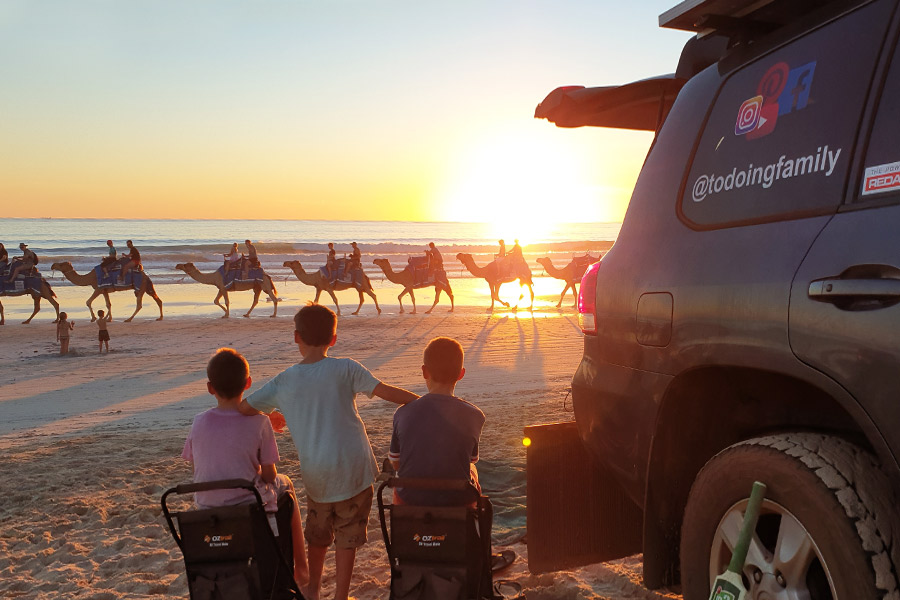 People riding camels along the beach as 3 boys watch from near their 4wd