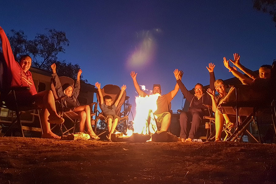 People raising their arms up while sitting around a campfire at night