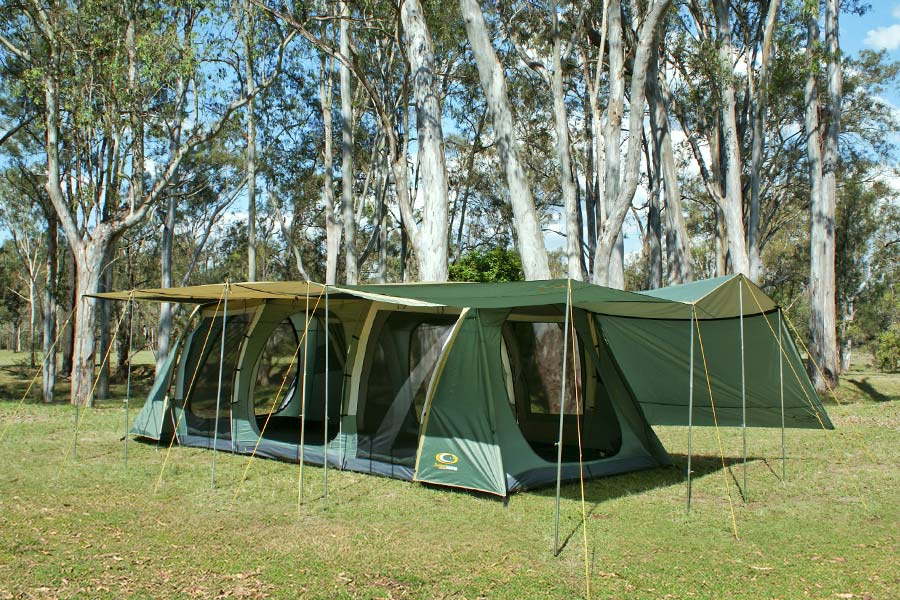 A large family tent with it's awnings fully set up on a grassy site.