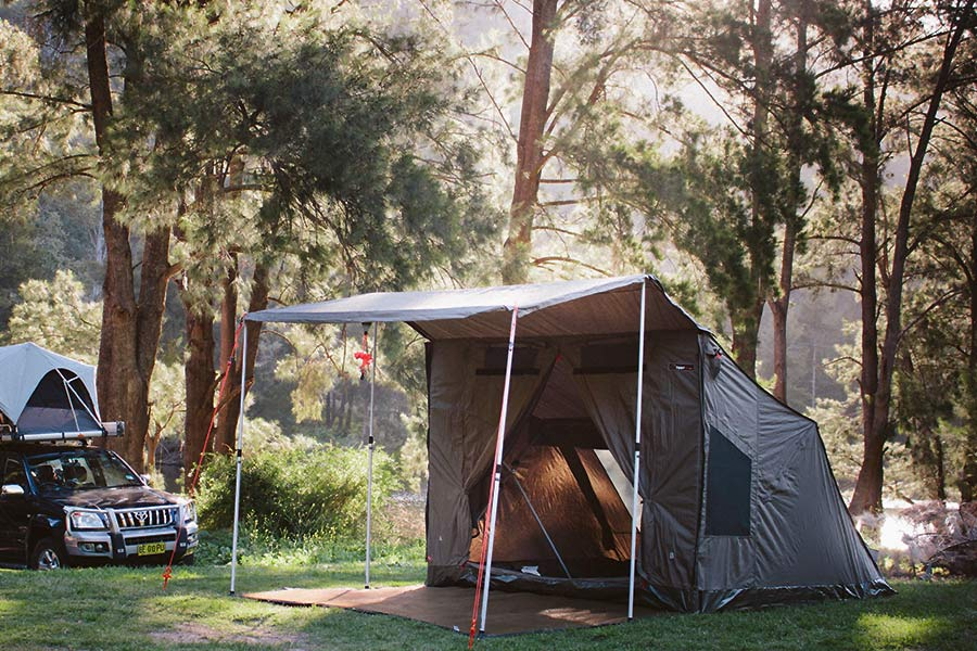 An Oztent RV5 set up at a campsite in the forest.