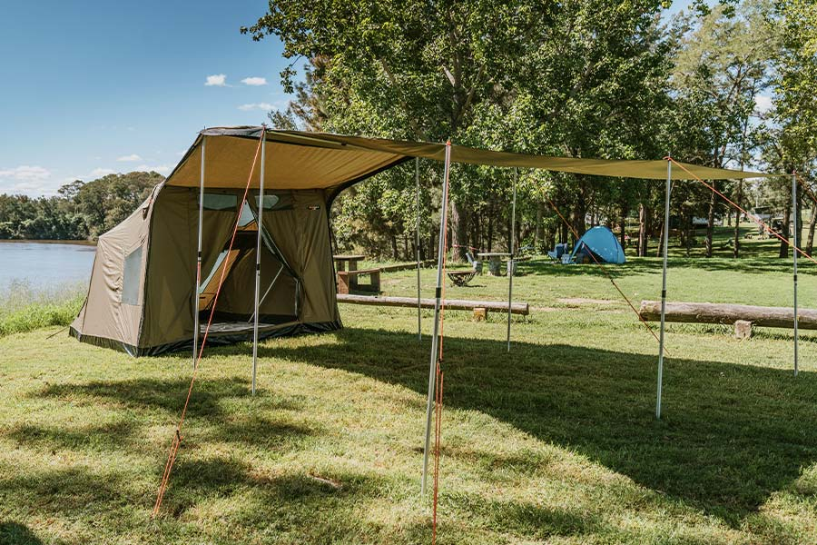An Oztent SV5MAX tent set up, with it's large tarp awning extension, at a grassy campsite by the river.