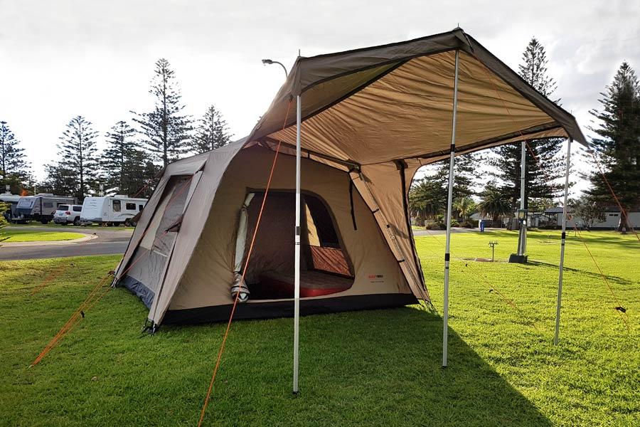 The Black Wolf Turbo Plus tent with it's large awning, set up on grass at a caravan park.