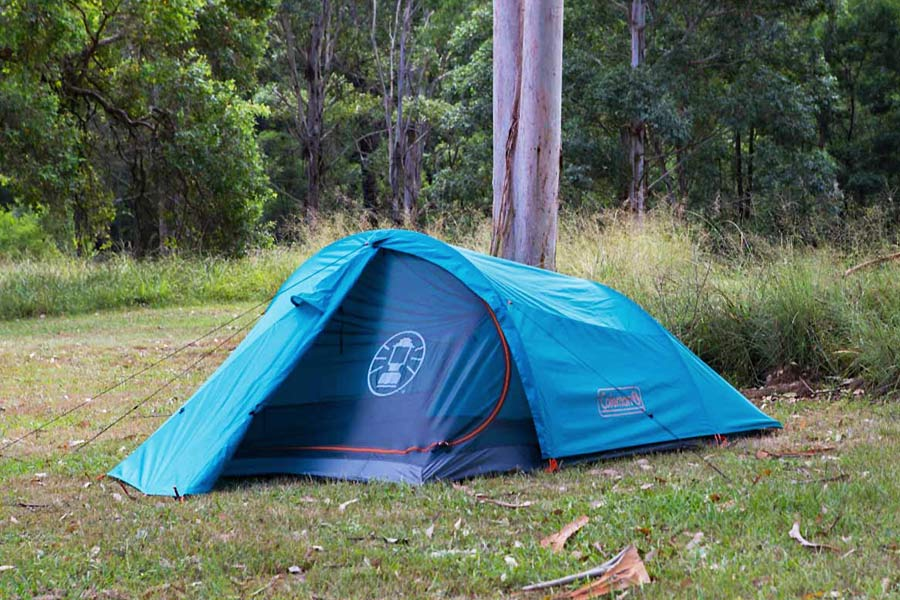 A blue hiking tent pitched on grass with trees behind.