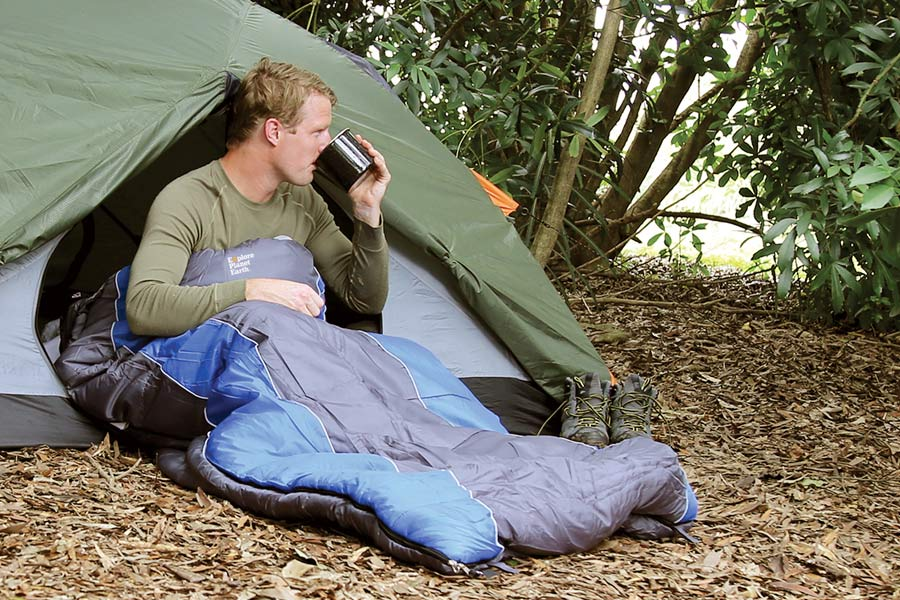 Man in sleeping bag sipping from a camp mug while sitting inside entrance to hiking tent.