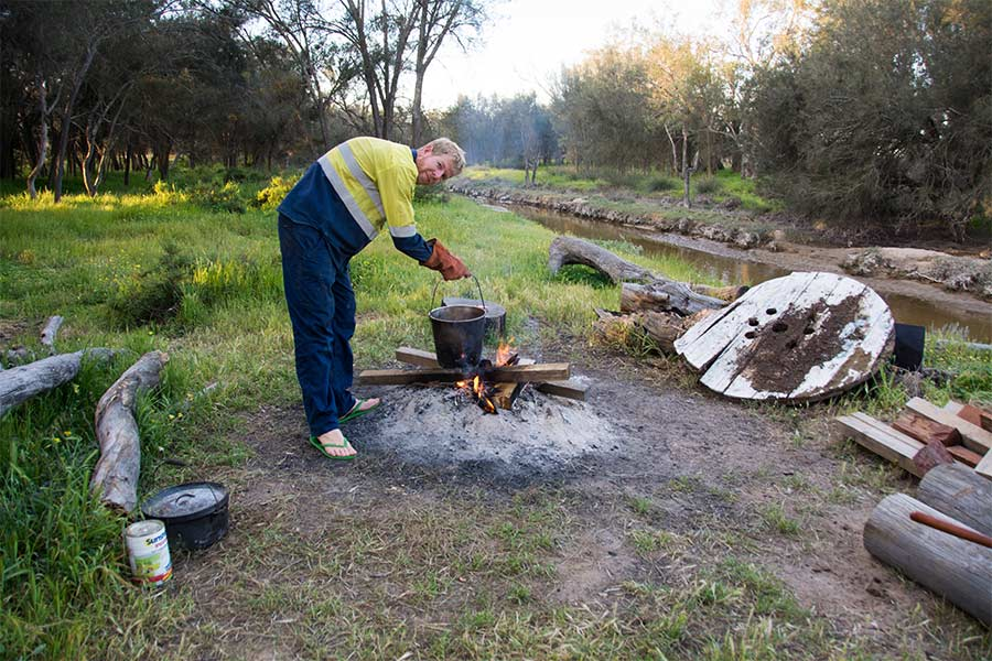 Man holding stainless steel bucket over campfire
