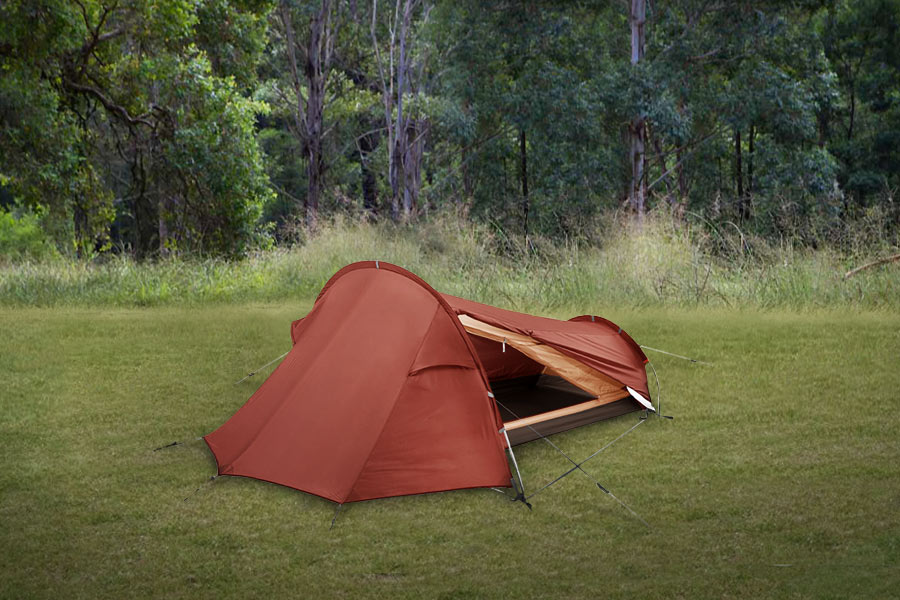 Red and orange Vaude hiking tent on green grass with trees behind.