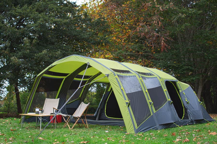 A large inflatable-pole tunnel-style tent from Zempire, set up on grass with chairs and a table at the awning entrance.