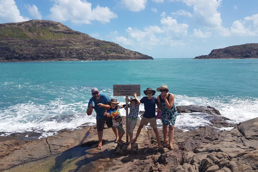 Family of 5 posing by sign at the northernmost point of Australia