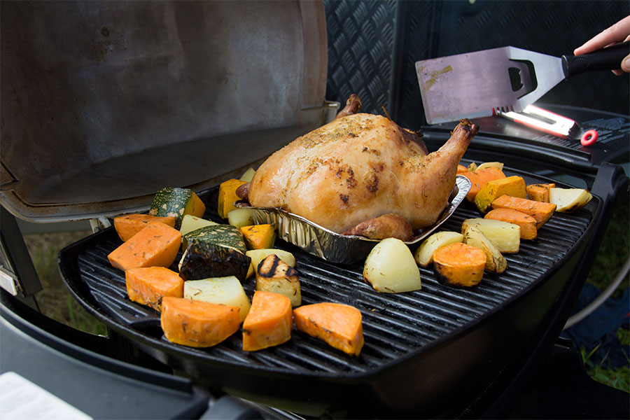 Roast chicken cooking on a grill with chopped vegetables cooking next to it