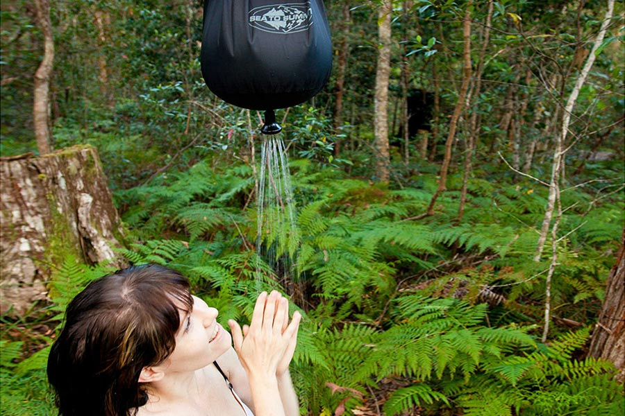 Woman showering under Sea to Summit Pocket Showerl 10 Litres
