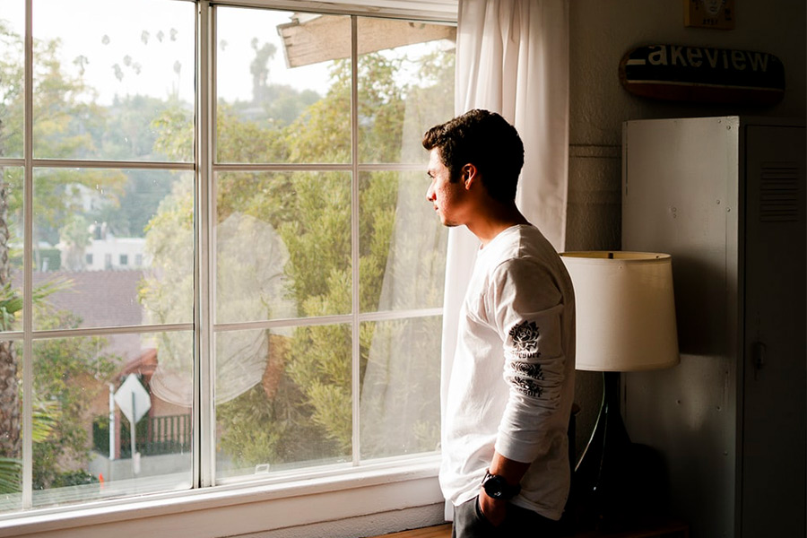 Man looking out the window while in self-isolation from a pandemic