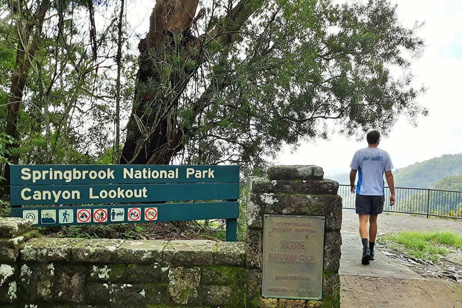 Man walking past Canyon Lookout sign