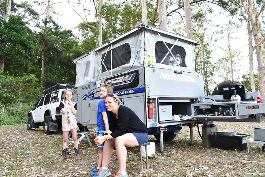 Family of 3 standing outside 4wd & camper trailer
