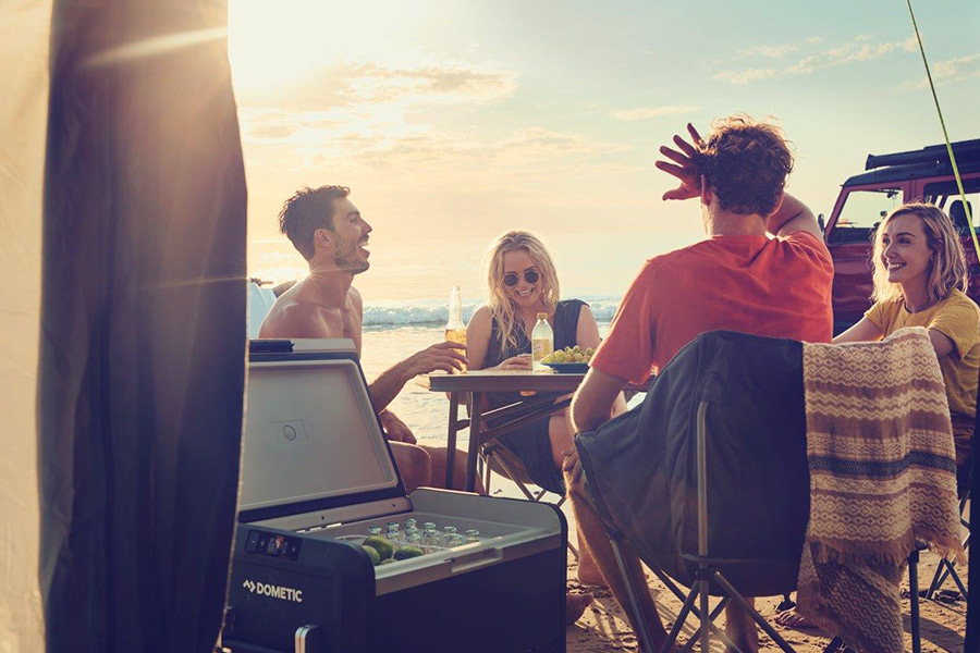 Group of four people sitting at a table by the beach with their Dometic CFX3 Fridge Freezer open next to them