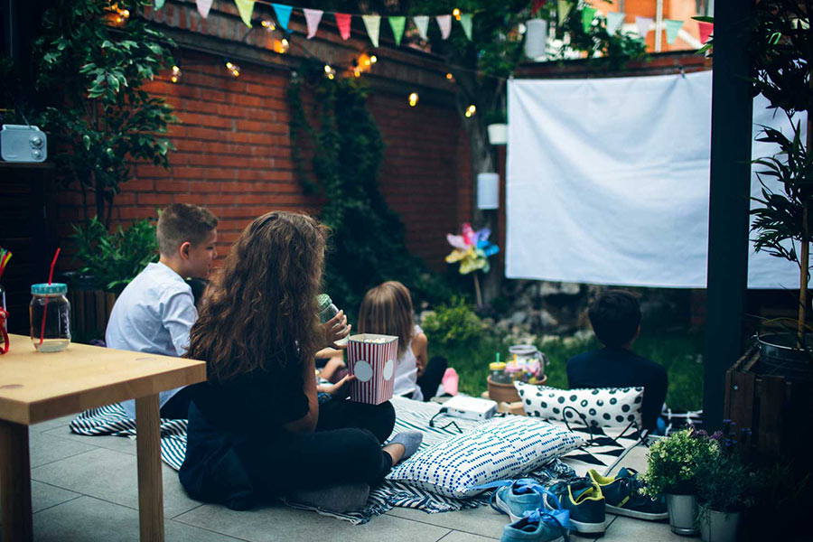 Kids watching a movie outdoors in their backyard