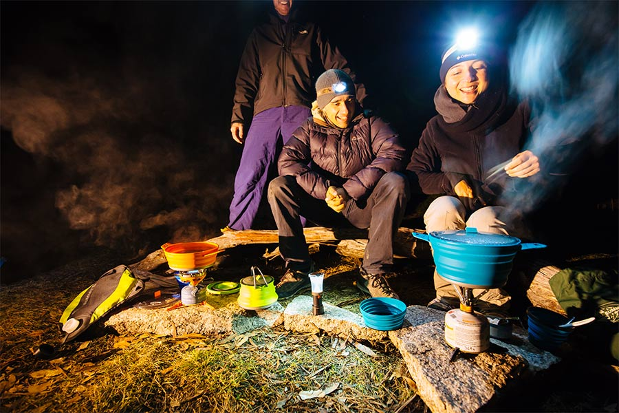 People cooking outdoors with Sea to Summit cooking products
