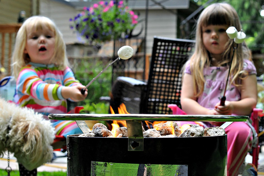 Two young girls toasting marshmallows in your backyard