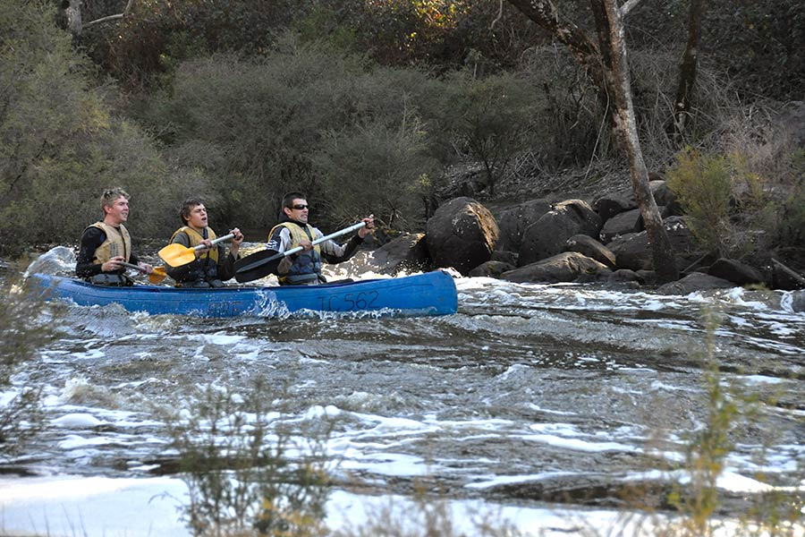 3 men in a canoe on a river, white water rafting