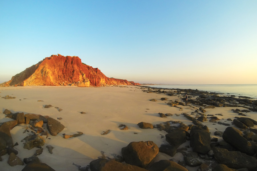 A red outcrop of rocks on a beach at sunset