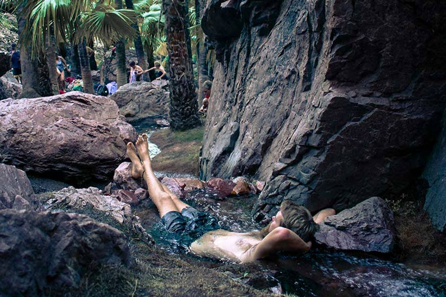 A man lies in a small rockpool in a gorge