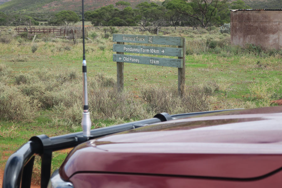 The bonnet of a 4WD with a signpost behind it