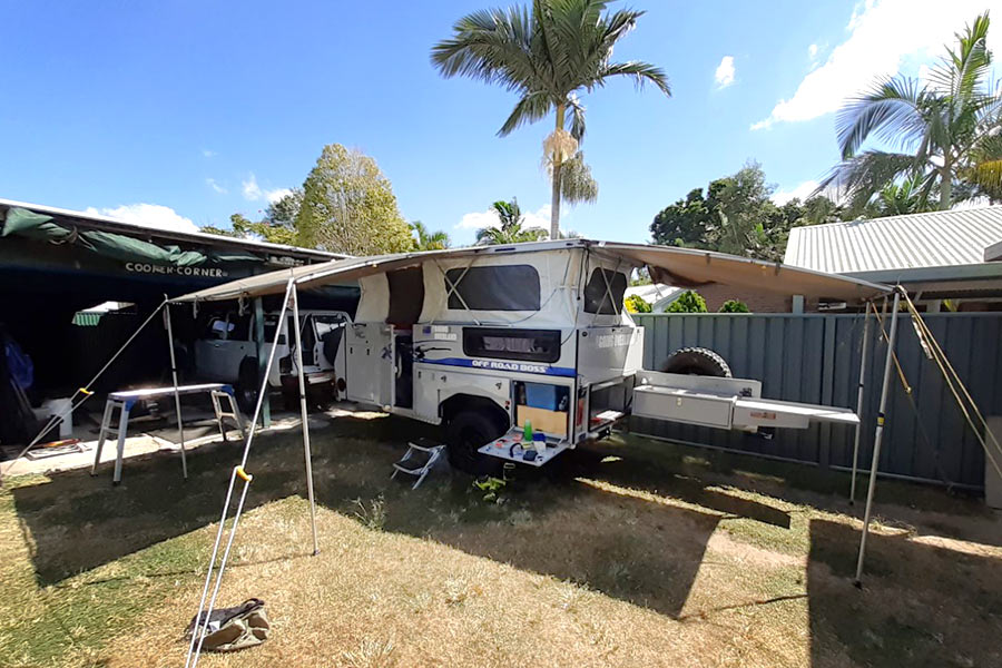 Pop-up caravan trailer set up with it's annex in a backyard