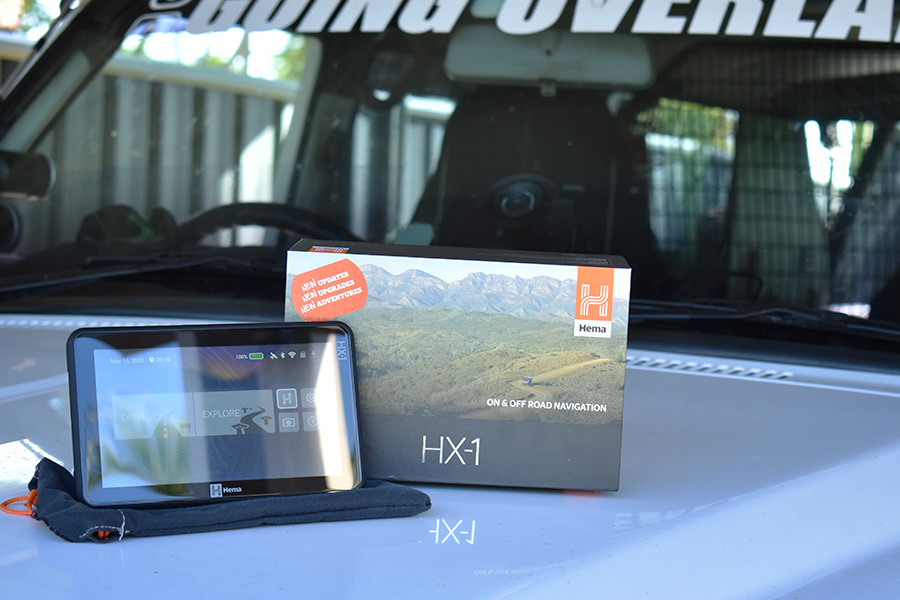 An on and off road navigator device alongside it's packaging on the bonnet of a 4WD