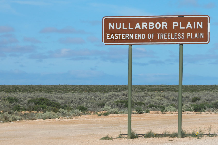 A sign on a dirt road in the outback that reads 'NULLARBOR PLAIN EASTERN END OF TREELESS PLAIN'