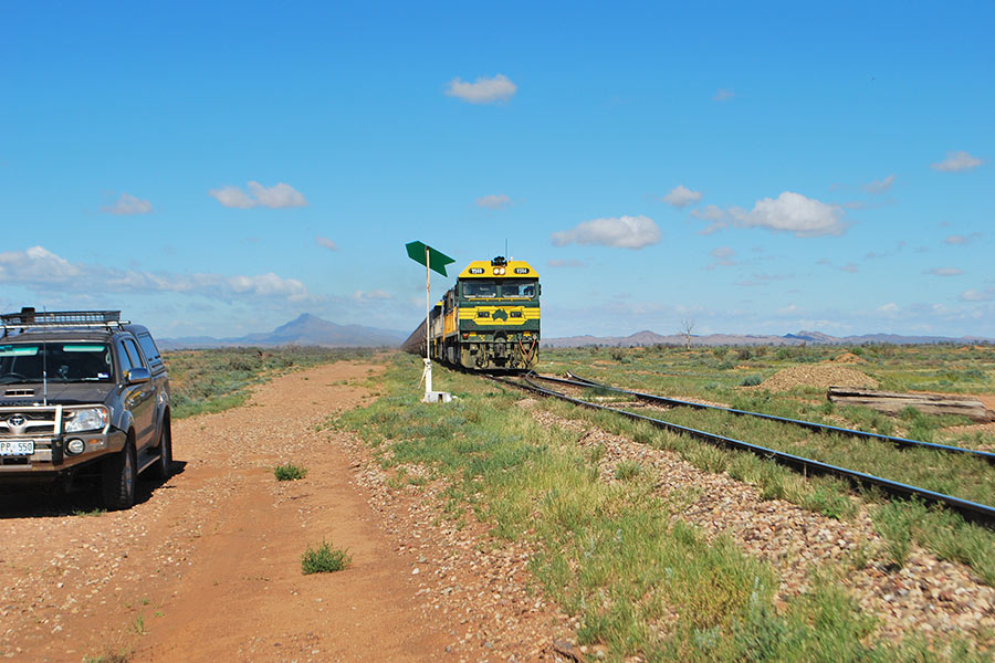 A 4WD is parked on the dirt next the railway tracks, with a train on the tracks and mountains in the distance