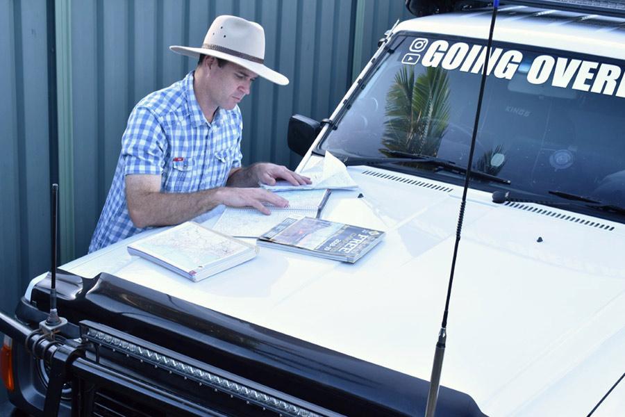 Man looking at maps on a car bonnet