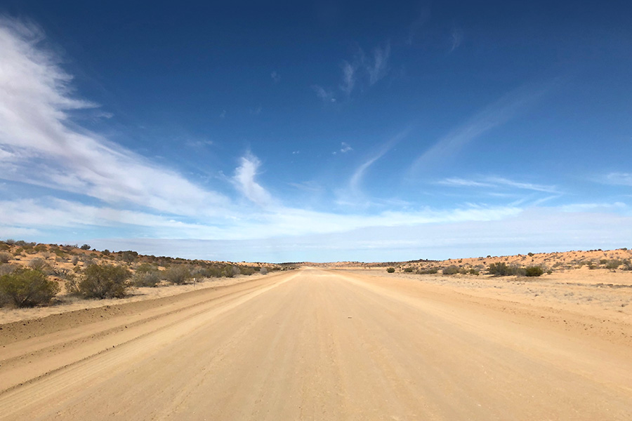 On the desolate dirt road with the large blue open sky