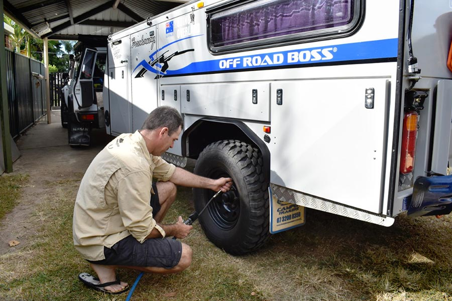 Man adding air to a camper trailer tyre