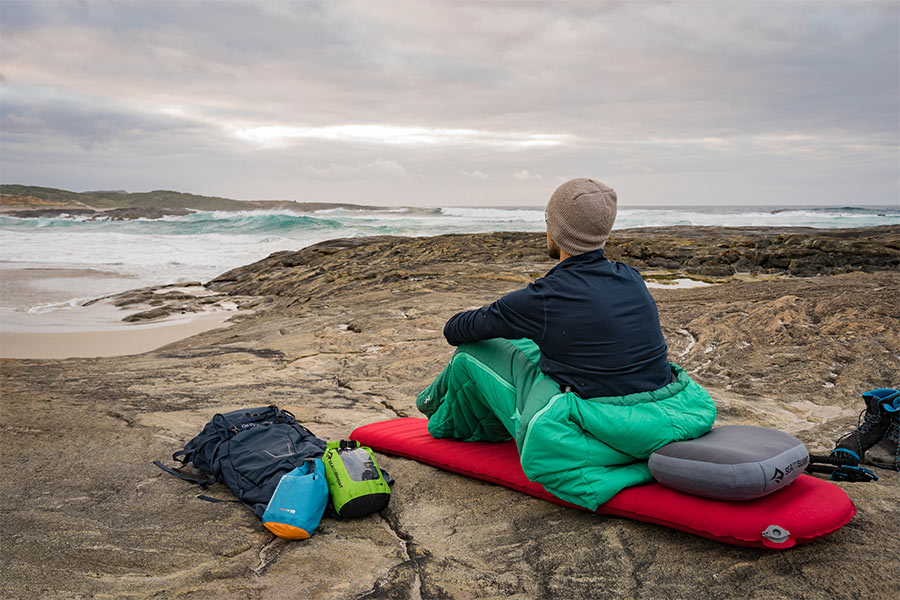 Person sitting on sleeping bag and mat outdoors