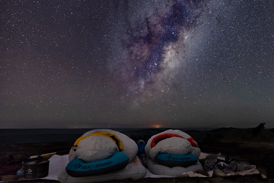 Two sleeping bags laid out under the stars at night