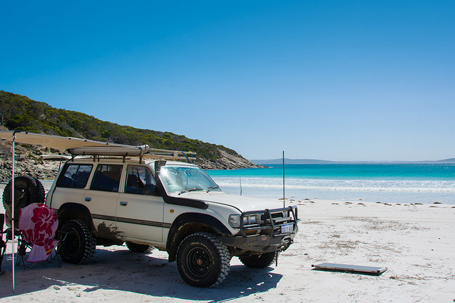 A 4WD parked on the beach with an open awning mounted from it's rooftop