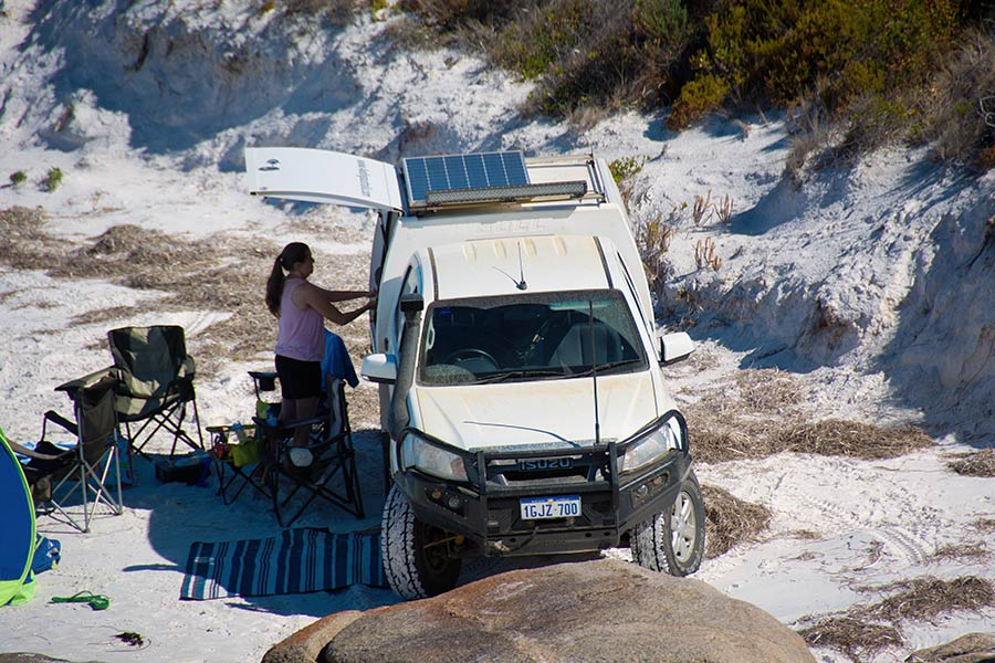 A 4WD parked on the sand with a woman accessing a drawer at an open side compartment