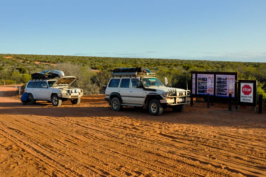 A couple of 4WD's parked next to a tyre pressure gauge on a remote sandy road