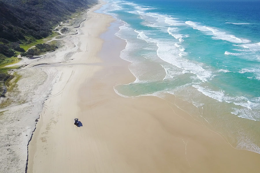 An aerial view of a 4WD on a wide sandy beach, with hills and ocean either side