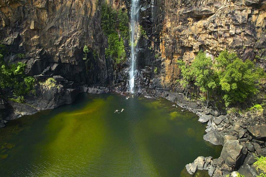 People float beneath a large waterfall along the Jatbula Trail