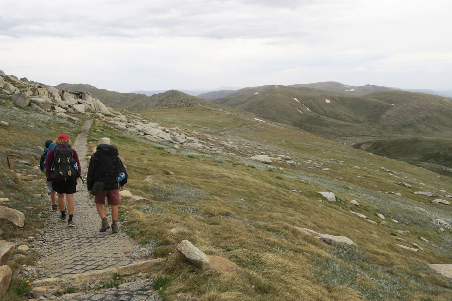 3 hikers walk along a paved trail on a grassy mountain range
