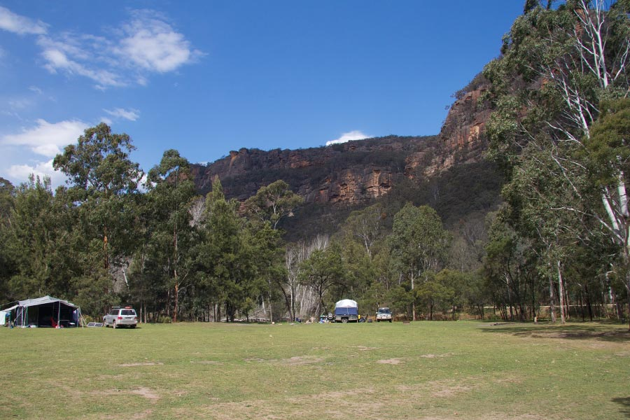 Campsites set up on a grassy clearing, surrounded by a rocky mountain