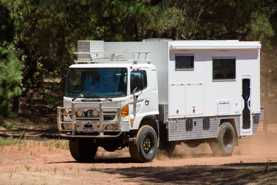 An offroad camper vehicle on a dirt road