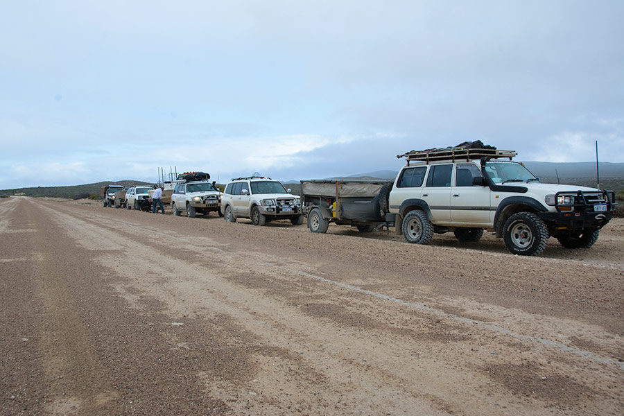 A convoy of 4WDs with their camper trailers parked by the side of a dusty road