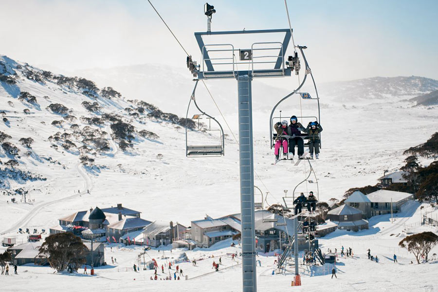 People sit in a ski lift above a ski resort and slopes
