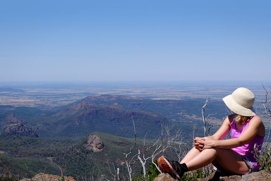 A woman sits on a clifftop looking out at the vast expanse of hills and plains below