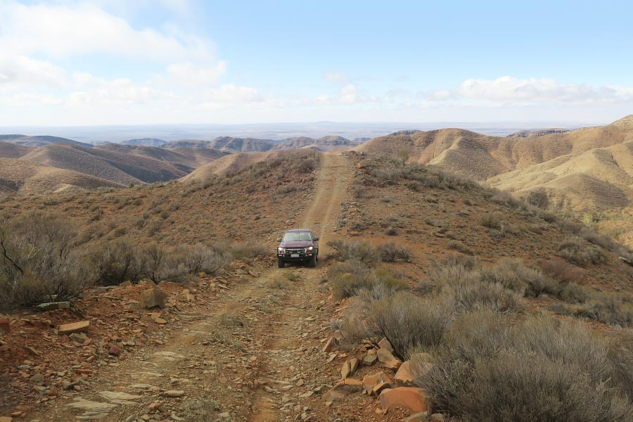 A car drives along a track with a view of ranges in the distance