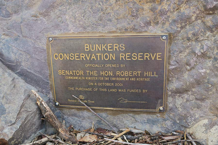 A sign attached to a large rock that reads BUNKERS CONSERVATION RESERVE