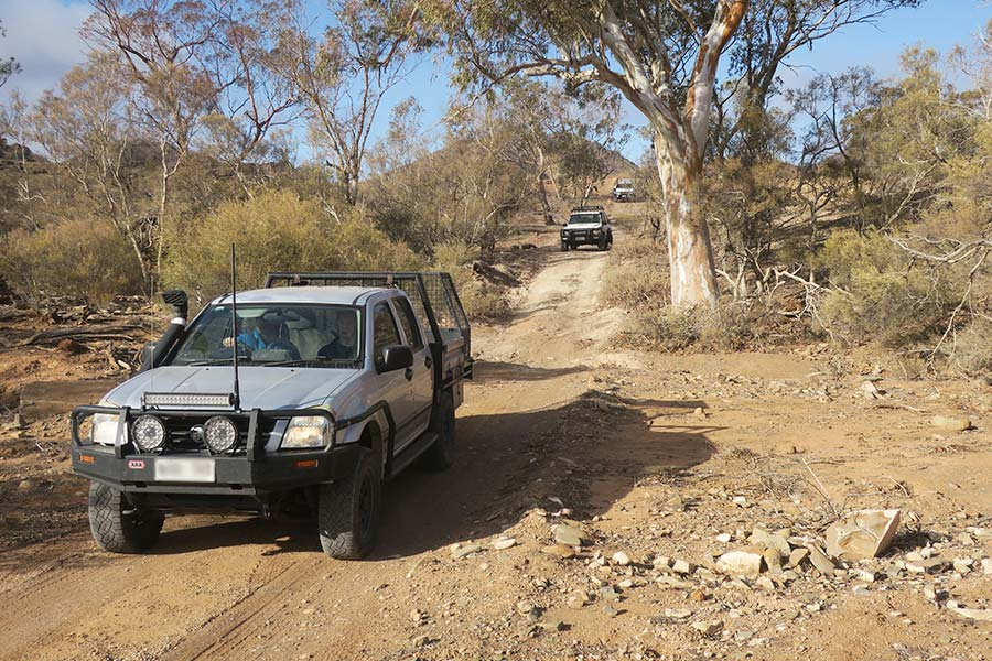 A convoy of 4WD's driving along a track that goes through creek beds